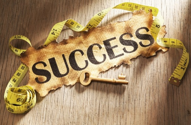 A burnt sheet of paper with the word Success written on it with a golden key underneath and yellow measuring tape surrounding it