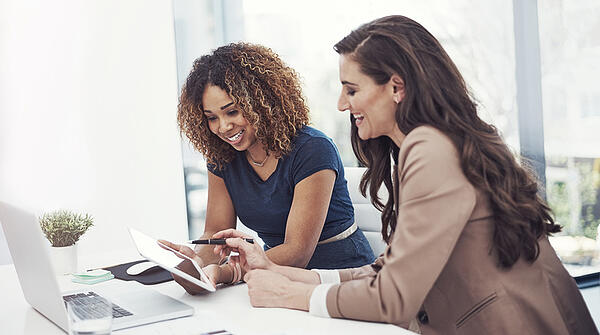 2 female meeting and event professionals sitting at a desk using a laptop and tablet