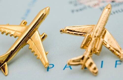 2 golden miniature airplanes placed on top of a world map
