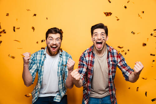 2 male superfans cheering and celebrating as confetti falls on top of them
