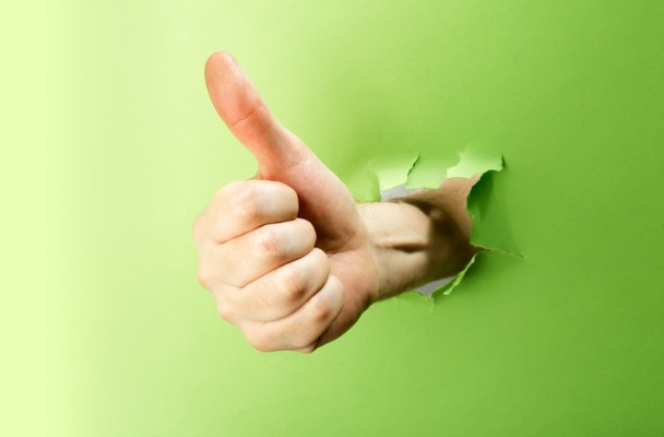 Hand holding the thumbs up signal punching through a green wall