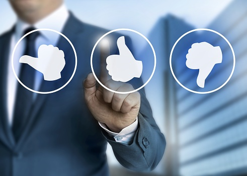 Businessman tapping on a thumbs up symbol