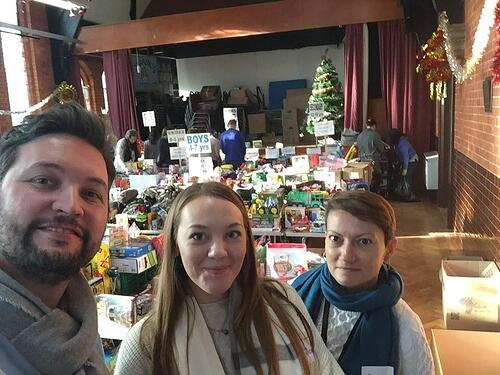 Aventri team members posing in front of toys and other donations that they were given to a local charity