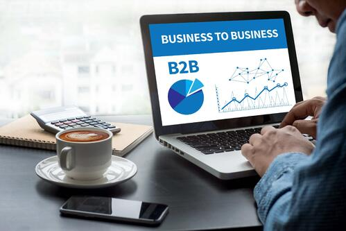 Male event professional looking at laptop screen that says B2B BUSINESS TO BUSINESS