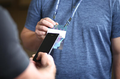 An attendee using their smartphone to scan another attendees badge at an event