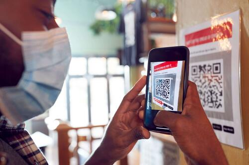 Man With Mobile Phone Scanning a QR Code at a venue during health pandemic