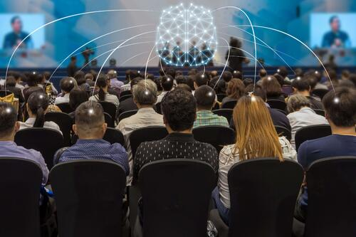 Picture of event attendee sitting at a conference highlighting how event intelligence is gathered before, during, and after an event.