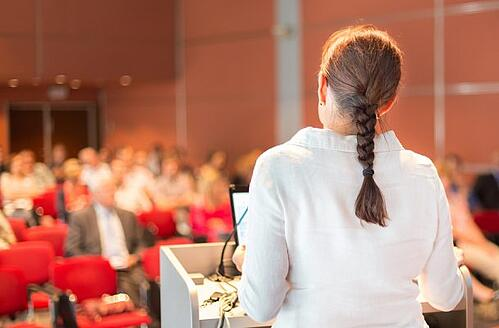 Female event planner standing at podium speaking at an event