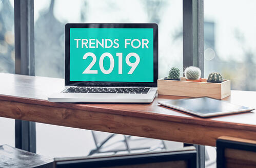 "Macbook pro on a table with the words ""Trends For 2019"" on the screen"