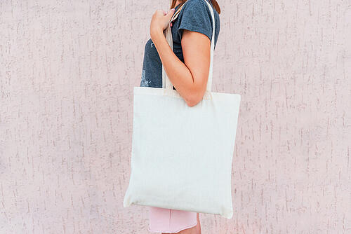 Woman wearing a white event swag bag around her shoulder