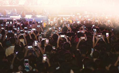 Attendees holding their mobile phones up anticipating  an event surprise