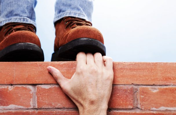Hand holding onto a brick ledge getting crushed by someone wearing brown boots