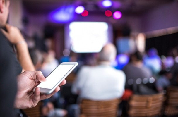 Event attendee holding a mobile phone while listening to a speaker at an event