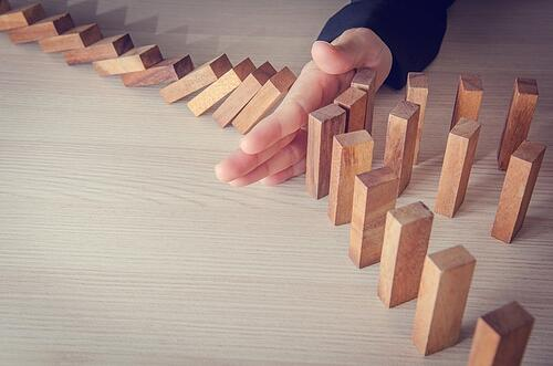 A hand stopping wooden dominoes from falling down