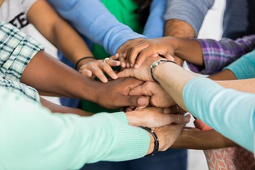 A group of individuals putting their hands in the middle of a circle