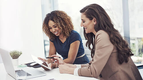 2 women sitting at a desk using a tablet to automate their events and meetings