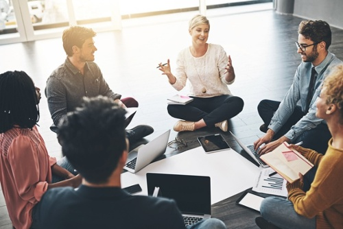 A group of business professionals sitting in a circle having a meeting