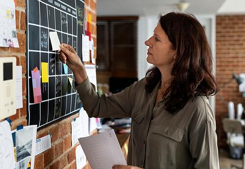 Woman multitasking with post-its all over a black chalk board