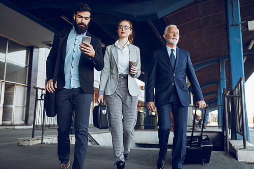 travel managers walking through airport with luggage in hand