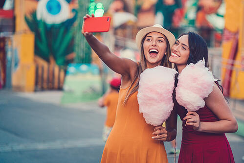 2 girls taking a selfie with pink cotton candy in their hands