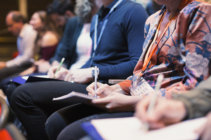 attendees writing in notepads