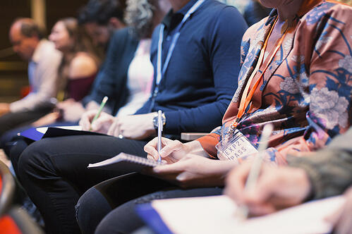 Attendees taking notes during an event session