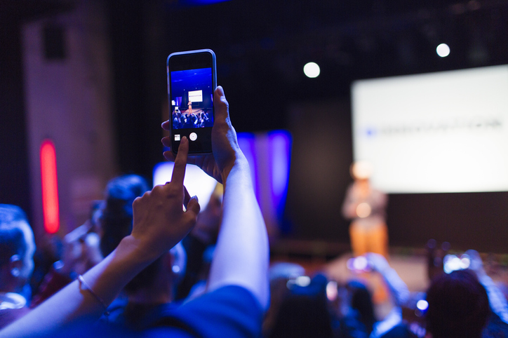 Attendee recording an event using their mobile phone