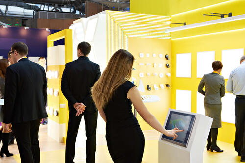 Female exhibitor engaging with a tablet while at a booth at a tradeshow