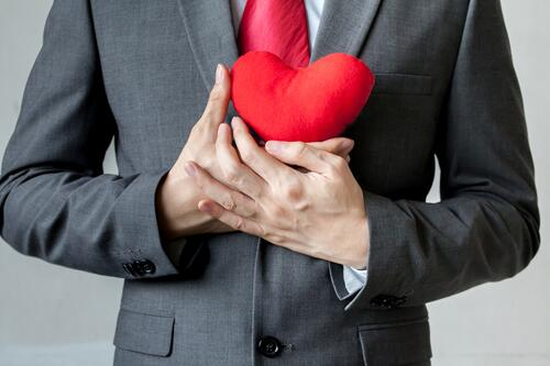 Male business professional holding a red heart in front of him to symbolizes that he's faithful a brand.
