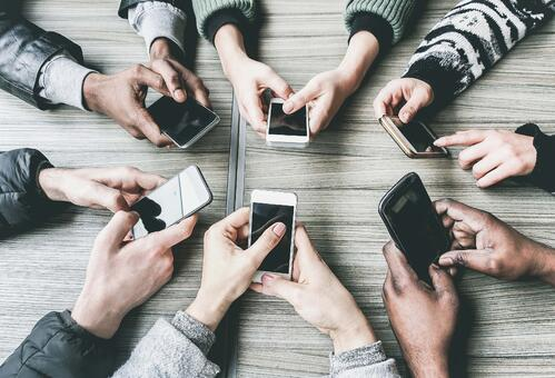 A group of individuals sitting around a table holding their mobile phones in their hands