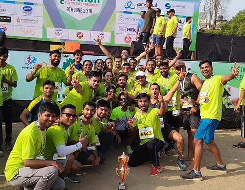 A group of runners posing after running in a fundraiser that promotes wellness by pushing participants to get active
