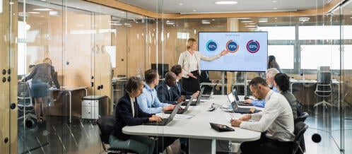A team of business professionals sitting around a conference table reviewing SMM metrics