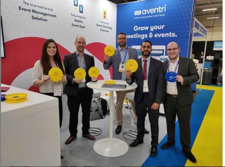 Aventri team giving attendees branded frisbees at a trade show