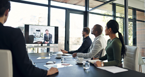 business professional gathered around a conference table having a virtual meeting