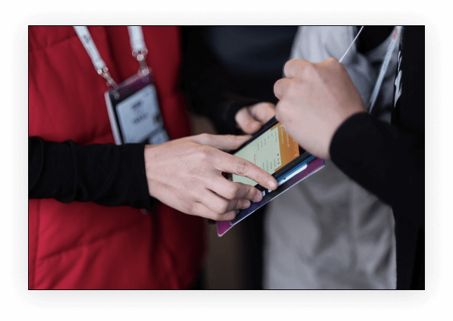 Business professional scanning an attendee's event badge with their smartphone to capture lead data