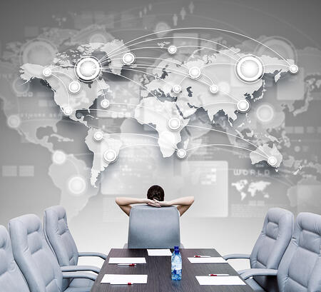Businesswoman in conference room sitting looking up at digital world map displaying her target audience