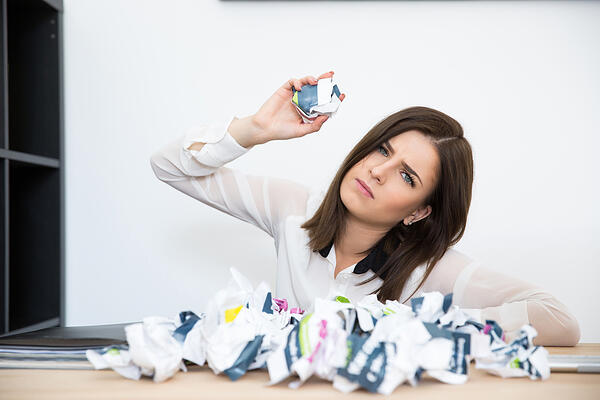 Female event meeting planner sitting at the table with trash paper