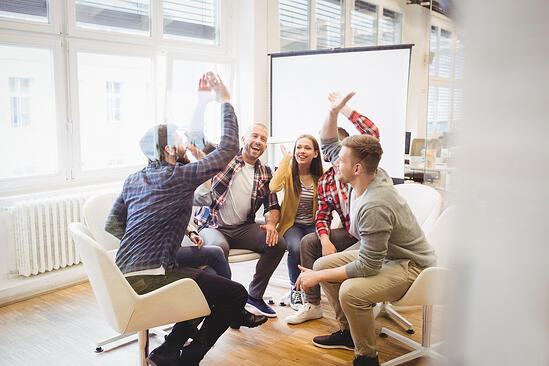Excited business people giving high-five in meeting room at an office