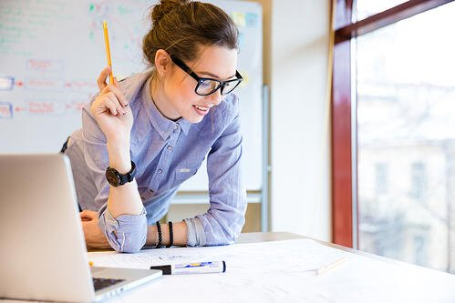 Happy young woman in glasses standing near the window in office working on her content marketing strategy