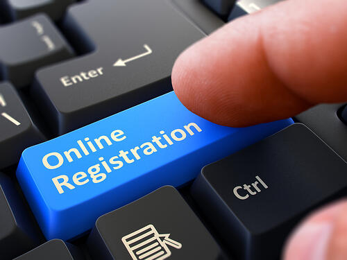 Online Registration - Written on Blue Keyboard Key. Male Hand Presses Button on Black PC Keyboard. Closeup View. Blurred Background.-1