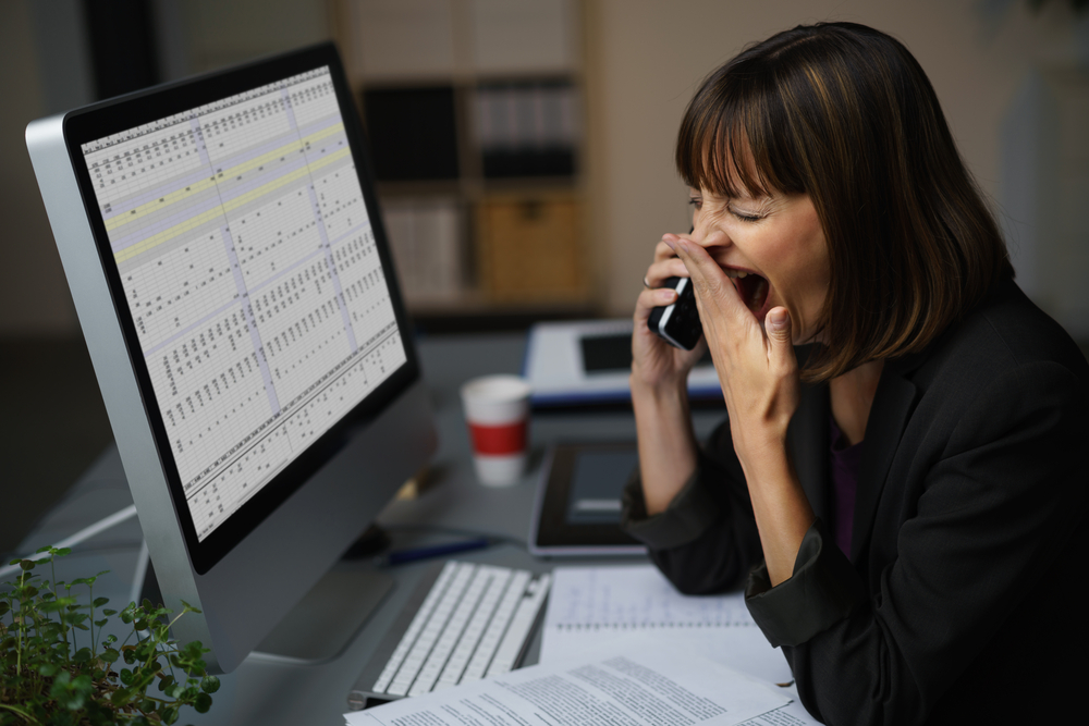 Tired businesswoman at her desk, showing yawning gesture while talking to someone on mobile phone.