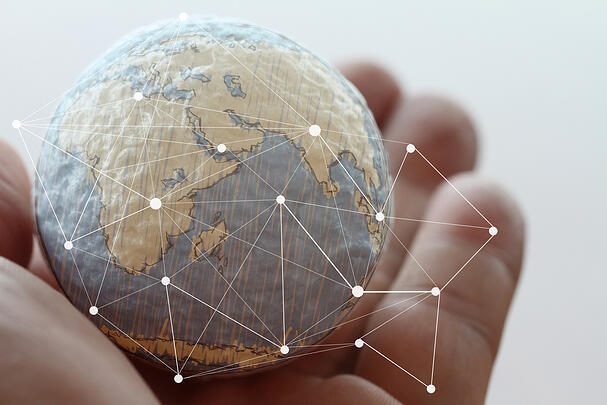 Close up of businessman hand holding the world with digital diagram signifying a globally active environment