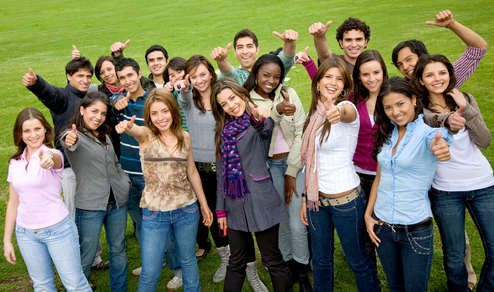 happy group of college students with thumbs up outdoors in a park