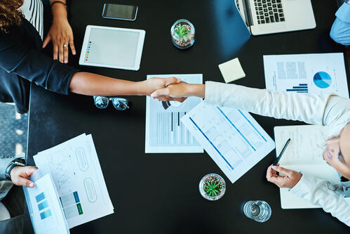 Meeting and event professionals shaking hands after making an acquisitions