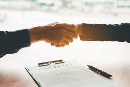 Business professional shaking hands after an acquisition