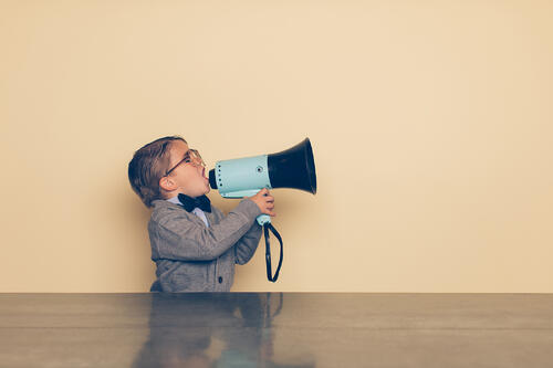 Small child building brand awareness by yelling into a megaphone