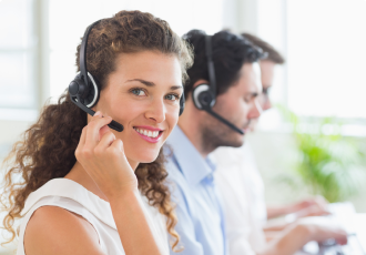Female support specialist wearing a headset assisting clients on the phone