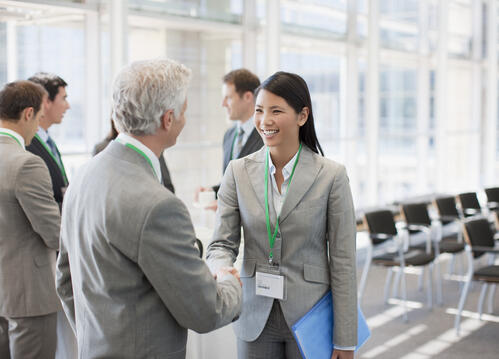 Attendees wearing event badges networking at a conference