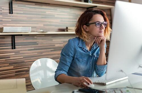 female event planner sitting at her desk doing research on customization options of her next event management for her organization