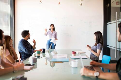 Female event professional giving a presentation to event sponsors on a whiteboard in a meeting room